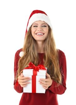 Довольно молодая дама в рождественской шляпе держит подарочную коробку на белом фоне