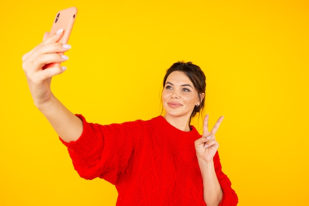 Довольно молодая дама в красном свитере держит телефон и фотографирует себя.
