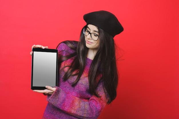 세련된 복장과 안경에 예쁜 아가씨가 웃고 밝은 빨간색 배경에 서있는 동안 빈 화면으로 현대 태블릿을 시연했습니다.