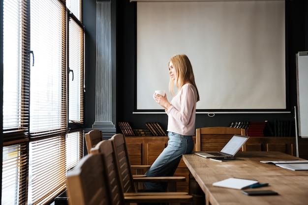 Довольно молодая леди, стоя в кафе работать с ноутбуком.
