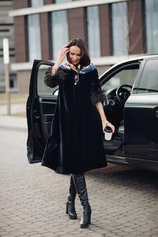 Bella giovane donna che indossa un cappotto nero alla moda mentre tiene il caffè e sta in piedi vicino all'auto. concetto di città della moda