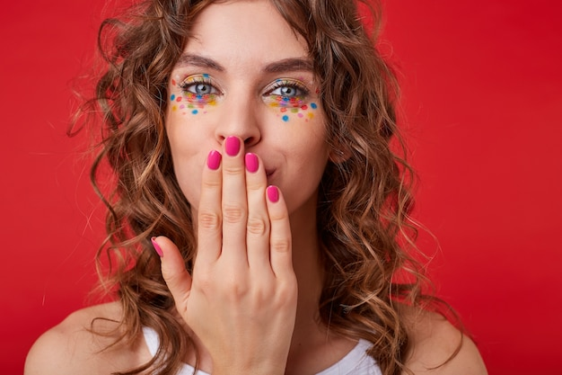 Pretty young lady with curls looks, kisses her hand with pink manicure, looks positive, stands