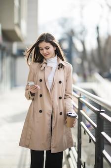 밝은 갈색 코트에 짧은 머리를 가진 예쁜 아가씨가 밖에 서 있습니다.