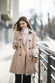 Pretty young lady with short hair in light brown coat is standing outside