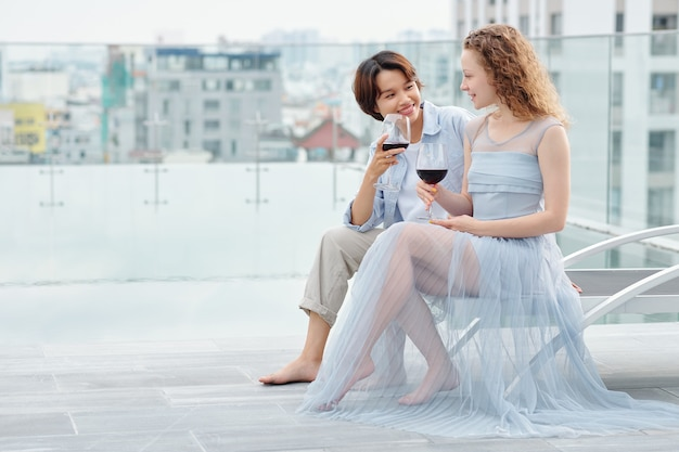 Pretty young lesbian women sitting on rooftop, talking and drinking tasty red wine