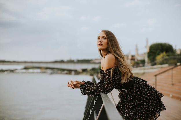 Довольно молодая женщина брюнетка длинные волосы стоя на берегу реки