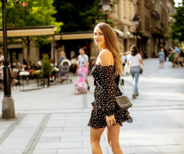 Довольно молодая брюнетка с длинными волосами идет по улице города