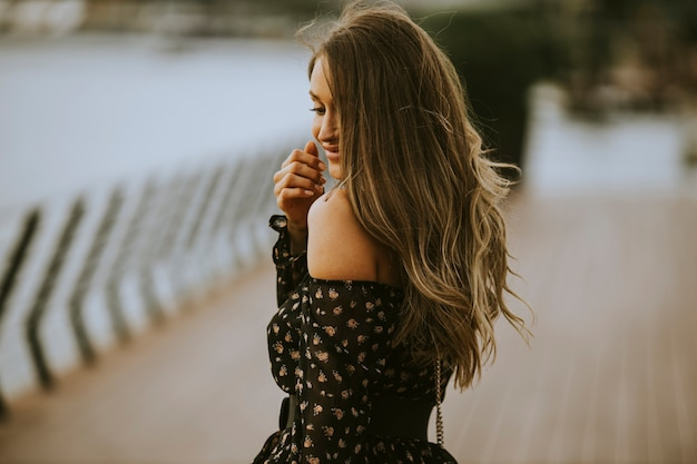 Pretty young long hair brunette woman walking on the riverside