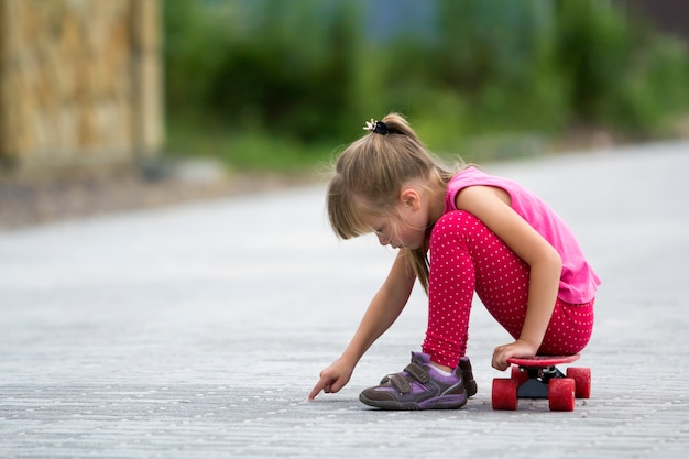 Pretty young long-haired blond child girl in casual pink clothing sitting on skateboard on paved suburb street