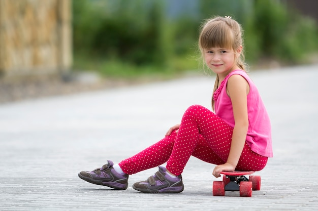 Pretty young long-haired blond child girl in casual pink clothing sitting on skateboard