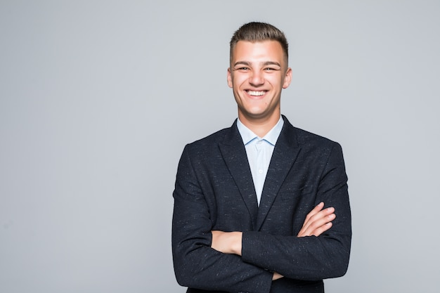 Uomo d'affari studente abbastanza giovane in giacca tiene le braccia incrociate isolato sul muro grigio chiaro