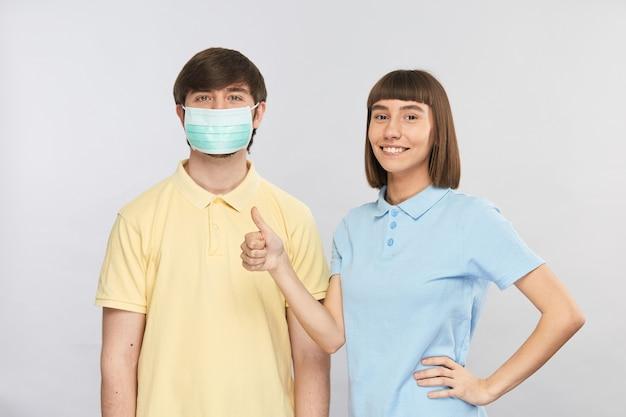 Симпатичный молодой человек в защитной маске и симпатичная девушка с улыбкой показывают жестом палец вверх, носят стерильные маски во время эпидемии или загрязнения воздуха