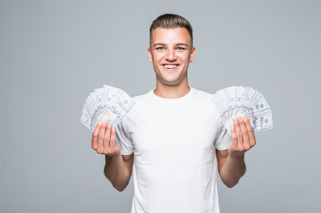 Pretty young man in white t-shirt hold a lot of dollar bills in his hands isolated on white background
