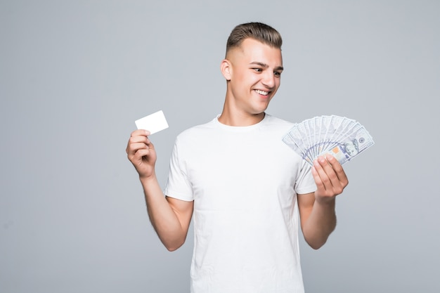 Pretty young man in white t-shirt hold a lot of dollar bills in his hands isolated on white