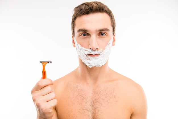 かみそりを持って頬に泡を剃っているかなり若い男