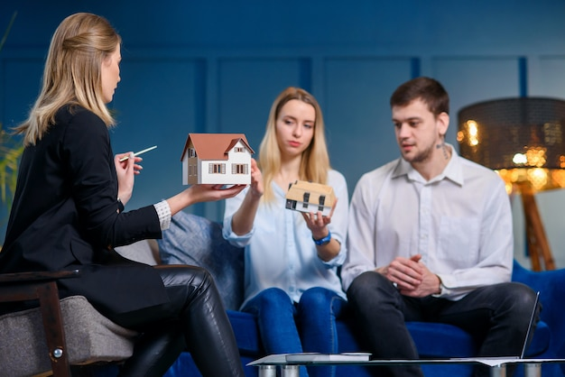 Pretty young man and woman discussing design of house with young female designer in the blue office.