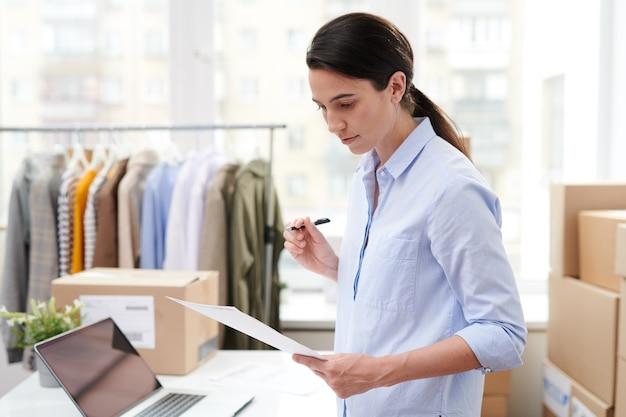 オンラインショップのかなり若いマネージャーは、注文を梱包する前に、クライアントの1人の商品のリストが記載された紙を読みます。