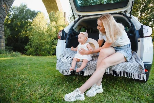 Довольно молодая супружеская пара и их дочь отдыхают на природе. женщина и девушка сидят на открытом багажнике машины.