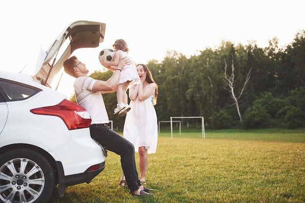 Pretty young married couple and their daughter are resting in the nature. the mother father and little girl are sitting on open car boot