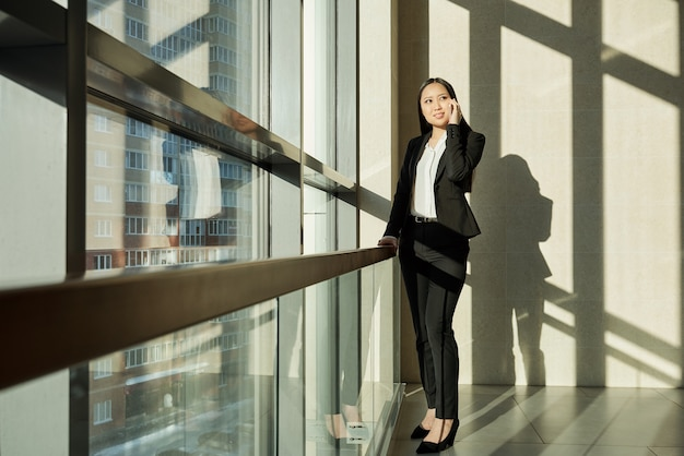 Pretty young mixed-race businesswoman in elegant suit standing by large window inside business center and talking on mobile phone