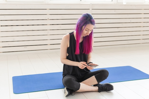 Симпатичная молодая девушка смешанной расы с фиолетовыми волосами подсчитывает сожженные калории с помощью приложения на своем смартфоне, сидя на спортивном коврике в тренажерном зале. концепция йоги и фитнеса.