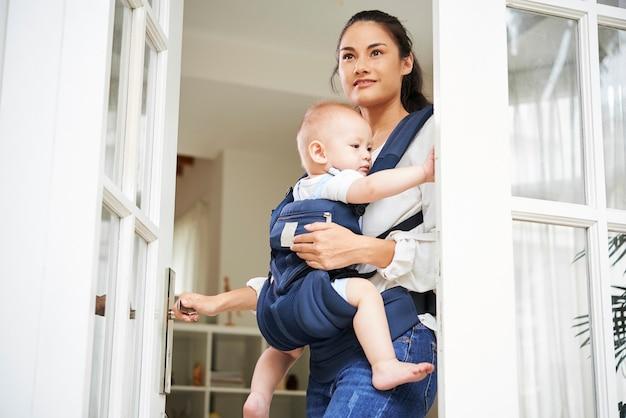 입구 문을 열고 캐리어에 아기와 함께 집을 떠나는 꽤 젊은 혼혈 여성