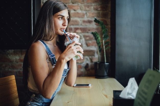 かなり若いモデルの女の子が窓の前のカフェに座って電話で働き、新鮮な飲み物を飲みます