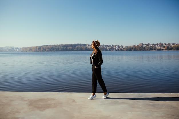Modello abbastanza giovane donna ragazza in posa in giornata autunnale in riva al lago vestita in abiti casual