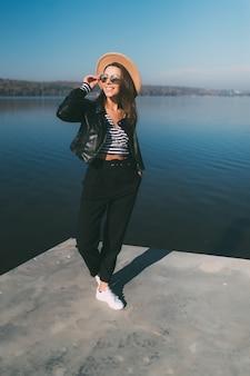 カジュアルな服を着て湖のウォーターフロントで秋の日にポーズをとるかなり若いモデルの女の子の女性