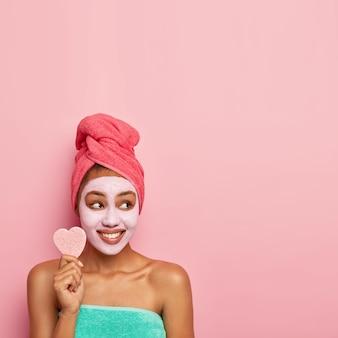 Симпатичная молодая модель с ухоженной кожей, носит маску для лица для уменьшения темных пятен и мешков под глазами, держит косметический спонж, на голове обернуто банное полотенце.