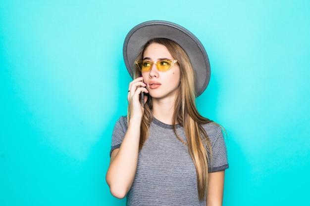 緑の背景に分離された電話でファッションtシャツ、帽子、透明ガラスのかなり若いモデル協議