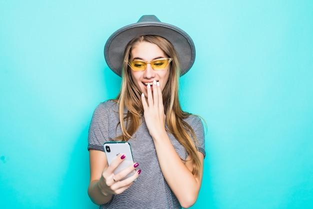 Довольно молодая модель в модной футболке, шляпе и прозрачных очках с телефоном в руках, изолированные на зеленом фоне