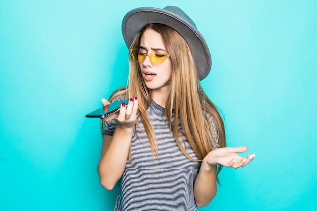 緑の背景に分離された彼女の手に電話でファッションtシャツ、帽子、透明ガラスのかなり若いモデル
