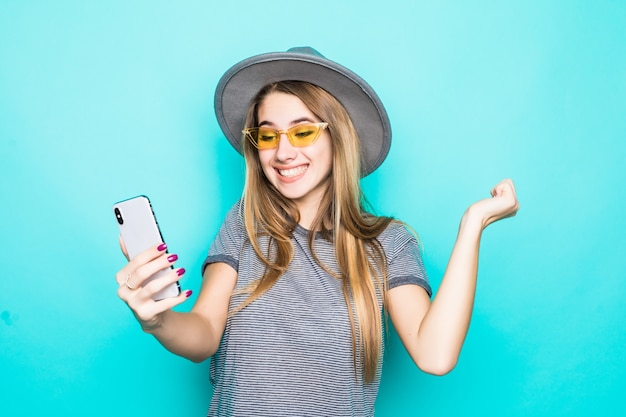 ファッションのtシャツ、帽子、彼女の手で携帯電話を持つ半透明のメガネでかなり若いモデルは、緑の背景に分離されたselfie