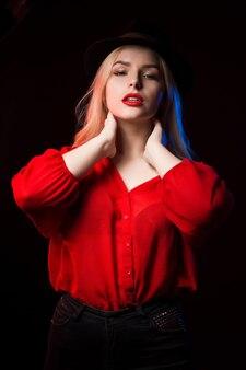 青と赤の光で影の中でポーズをとる赤い唇を持つかなり若いモデル