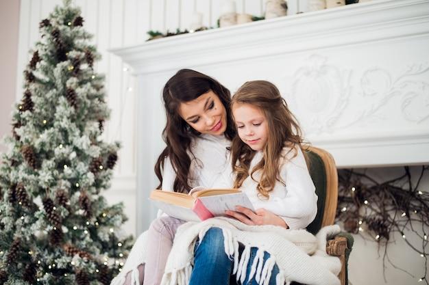 Довольно молодая мама читает книгу своей милой дочери возле дерева в помещении