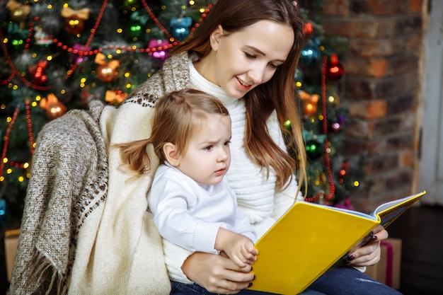 Pretty young mom reading a book to her cute daughter near christmas tree indoors