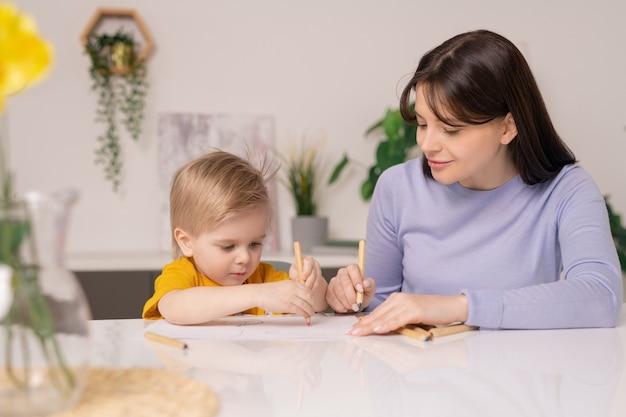 検疫期間中に家にいる間、かなり若い母親と彼女のかわいい幼い息子がカラフルなクレヨンで絵を描く