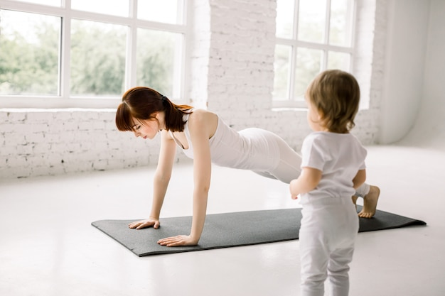 Pretty young mother fit and play yoga, doing plank for lose weight together with the little baby in big light gym