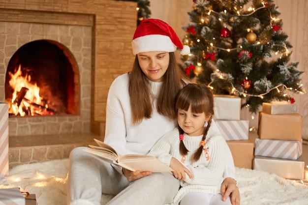 お祝いのリビングルームで暖炉とモミの木の近くに座って娘に本を読んでいるかなり若い母親
