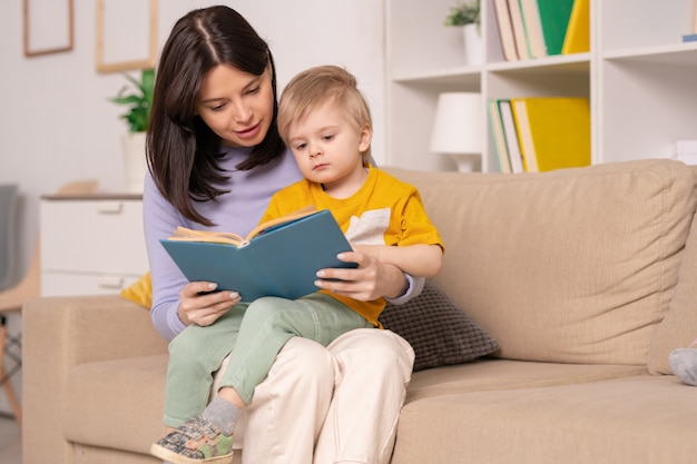 Pretty young mother reading her little son book of fairy tales while holding him on knees during home rest or self-isolation