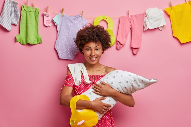 Pretty young mother with afro hair, holds newborn baby wrapped in blanket, rubber bib for feeding infant expresses love and care stands