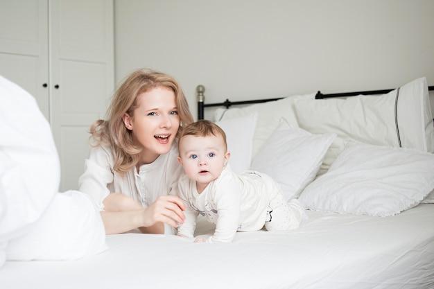 ベッドに幼い息子を持つかなり若い母親。面白い笑顔の朝。白い寝室