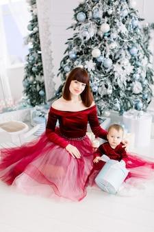 크리스마스 장식과 전나무 나무 앞에 앉아 어린 소녀와 함께 꽤 젊은 어머니