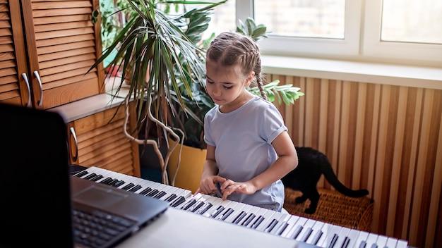 自宅でのオンライン授業中に自宅でクラシックなデジタルピアノを演奏するかなり若いミュージシャン、検疫中の社会的距離、自己隔離、オンライン教育の概念