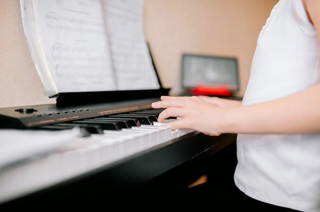 Довольно молодой музыкант играет на классическом цифровом пианино дома во время онлайн-урока дома