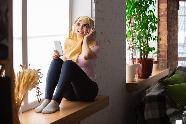 셀카 또는 화상 통화, 온라인 수업을 위해 태블릿을 사용하여 격리 및 자기 절연 중 집에서 꽤 젊은 무슬림 여성