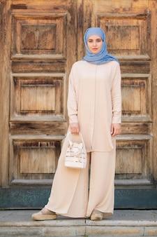ヒジャーブとスタイリッシュなカジュアルスーツのかなり若いイスラム教徒の女性が古代都市でなごむひと休みしながら白い革製のハンドバッグを保持