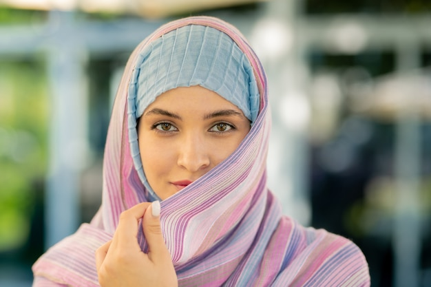 Pretty young muslim woman in traditional hijab looking at you while spending time outdoors
