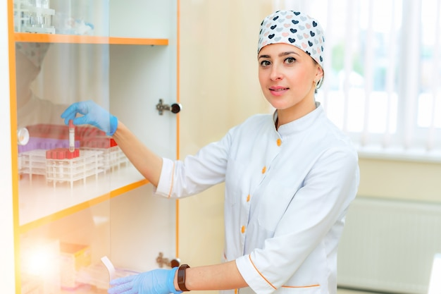 Pretty young nurse puts a test tube with the blood analysis into a special rack. portrait of a medical worker in white uniform and beautiful hat with red hearts in a modern laboratory.